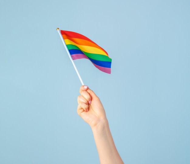 closeup-hand-waving-small-rainbow-flag-against-light-blue_93675-26590