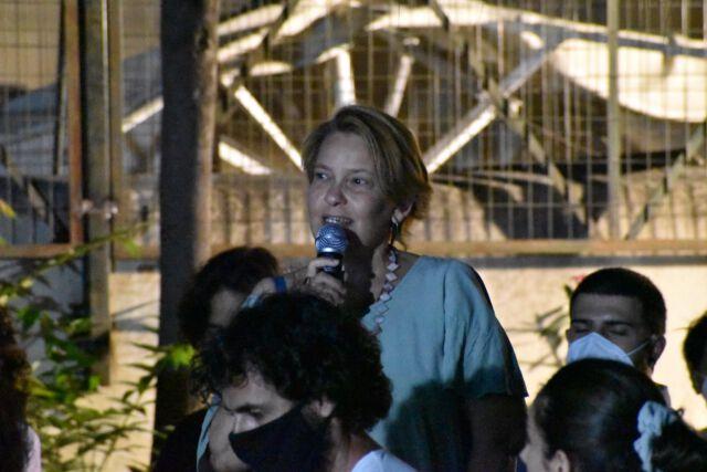 Η Μαίρη Χιόνη μιλά όρθια από το κοινό με φορητό μικρόφωνο, έχει ανοιχτόχρωμα κοντά μαλλιά, φορά ανοιχτόχρωμη μπλούζα και μακρύ κολιέ.