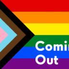H rainbow σημαία, με τα χρώματα της τρανς σημαίας και τις δύο black lives matter λωρίδες (καφέ, μαυρη) αριστερά. Στο κάτω δεξιά μέρος με άσπρα γράμματα γράφει coming out